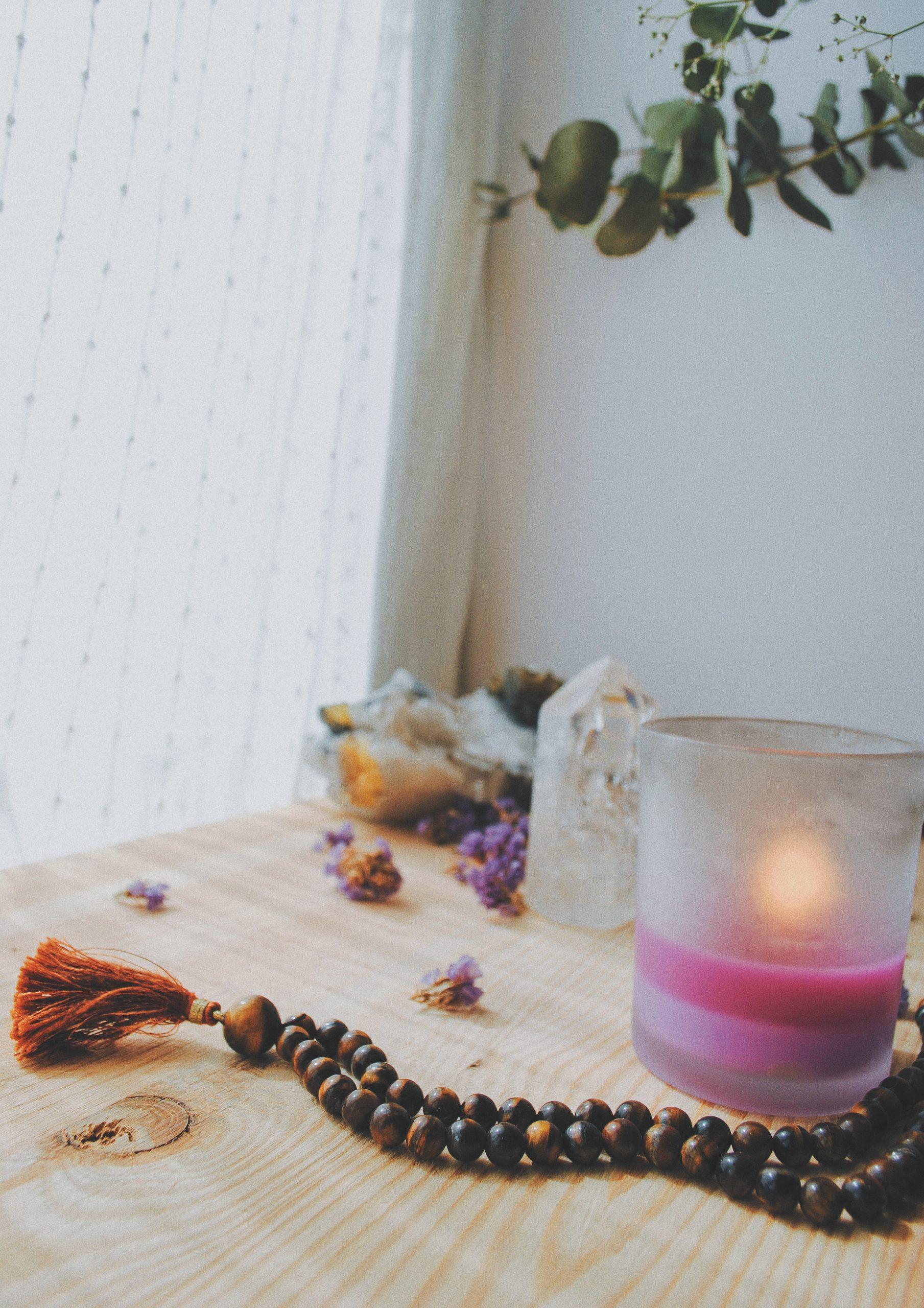 mesa con flores, incienso, una vela, piedras y un mala de meditación