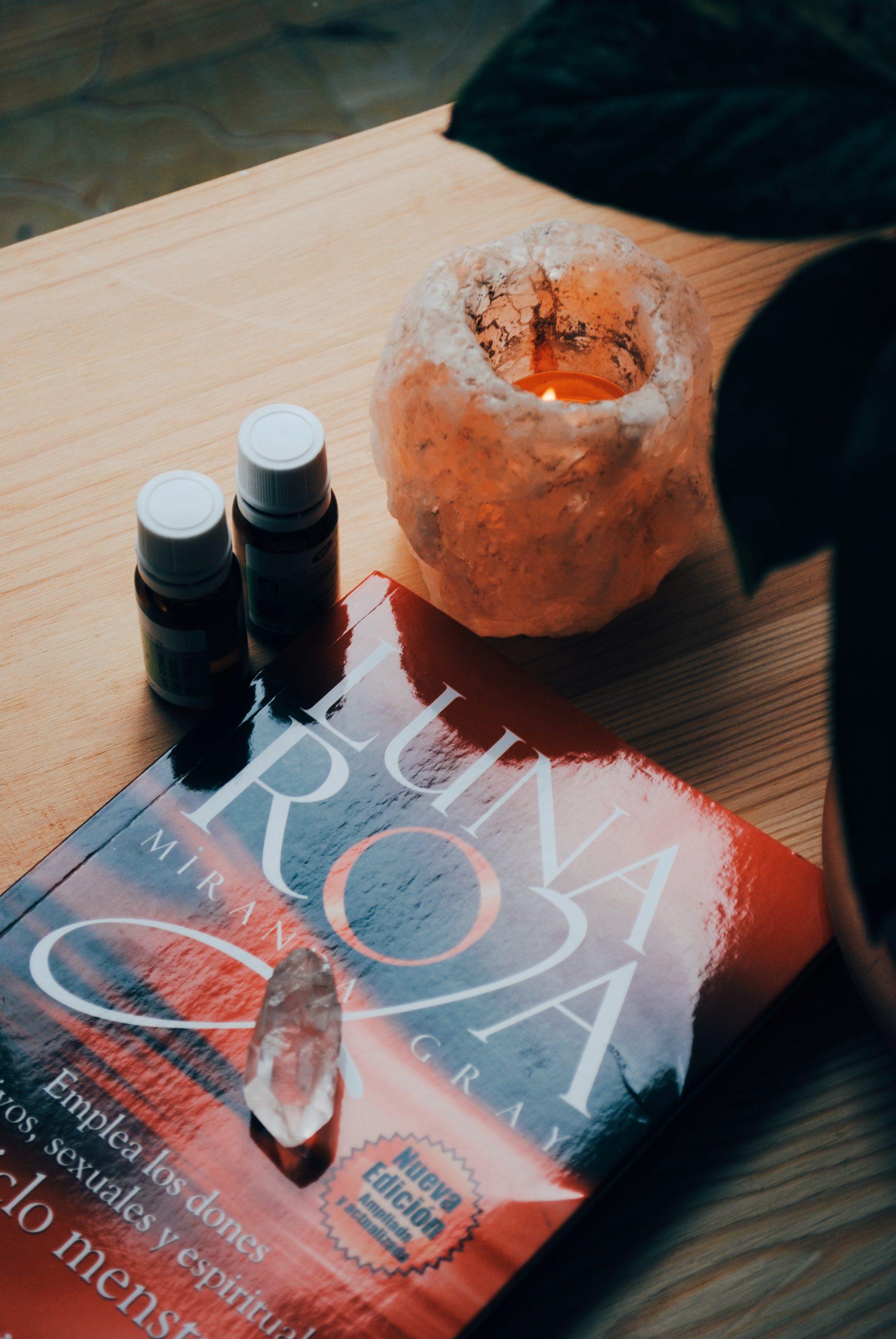 Libro luna roja, con vela encendida en portavelas de sal del himalaya, punta de cuarzo, botes de aceites esenciales y planta