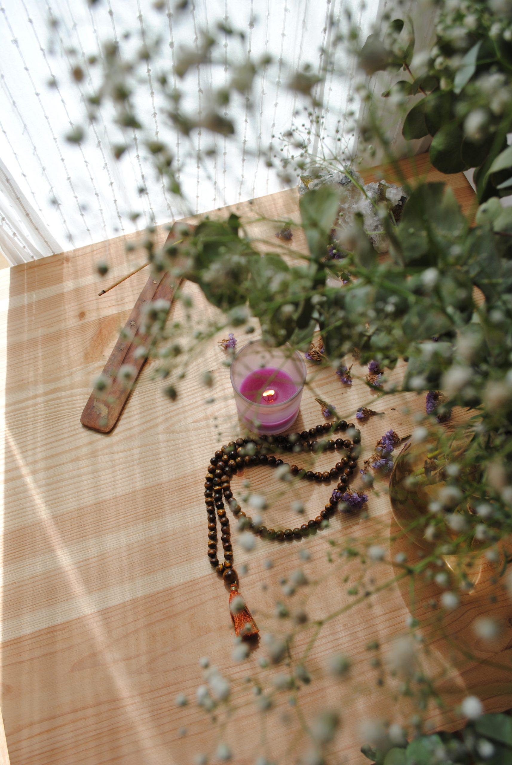 Mesa de madera con flores, una vela, incienso y un mala de meditación