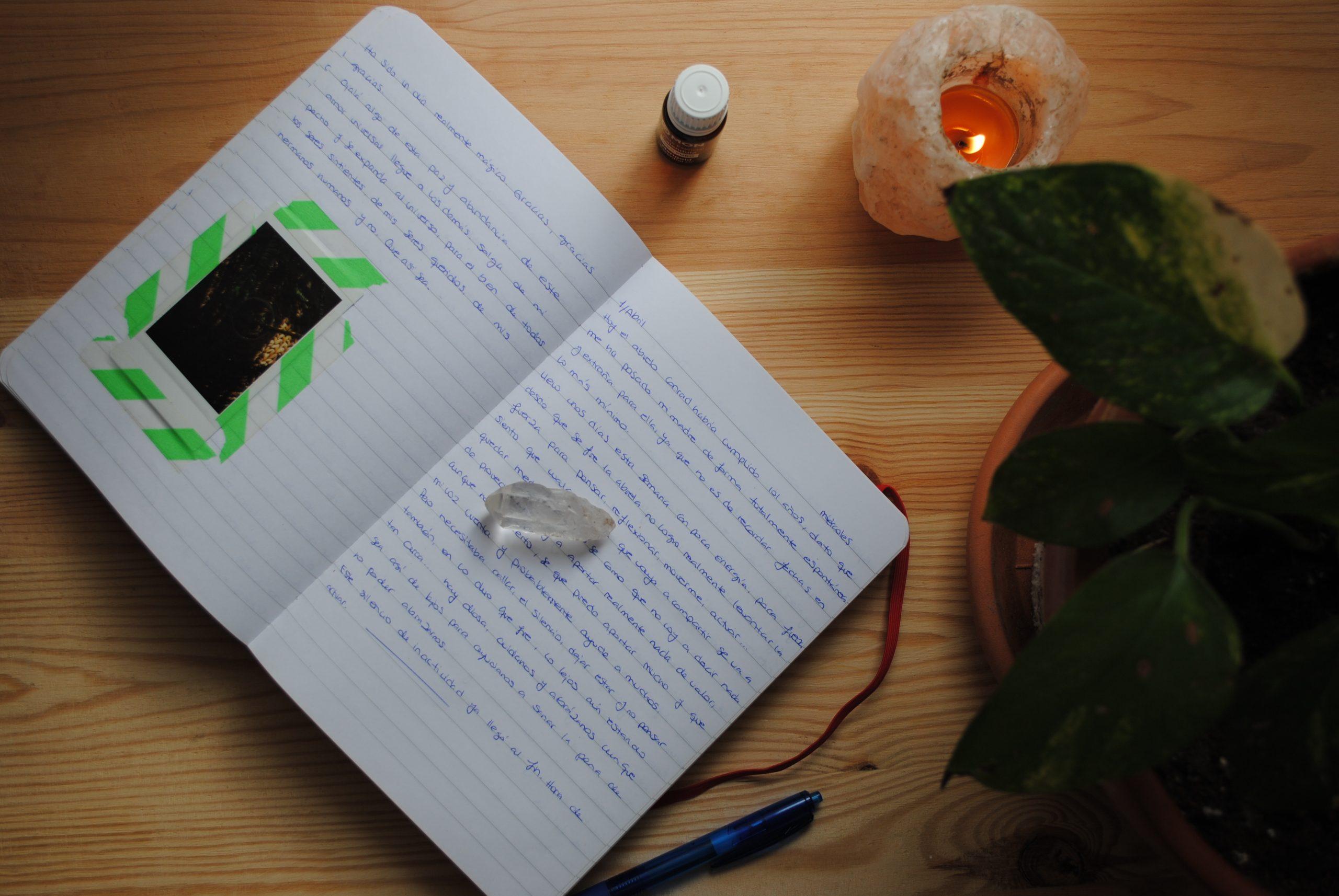 Libreta abierta de escritura terapáutica sobre mesa de madera. Punta de cuarzo, quemador de sal del himalaya con vela encendida, aceite esencial y planta