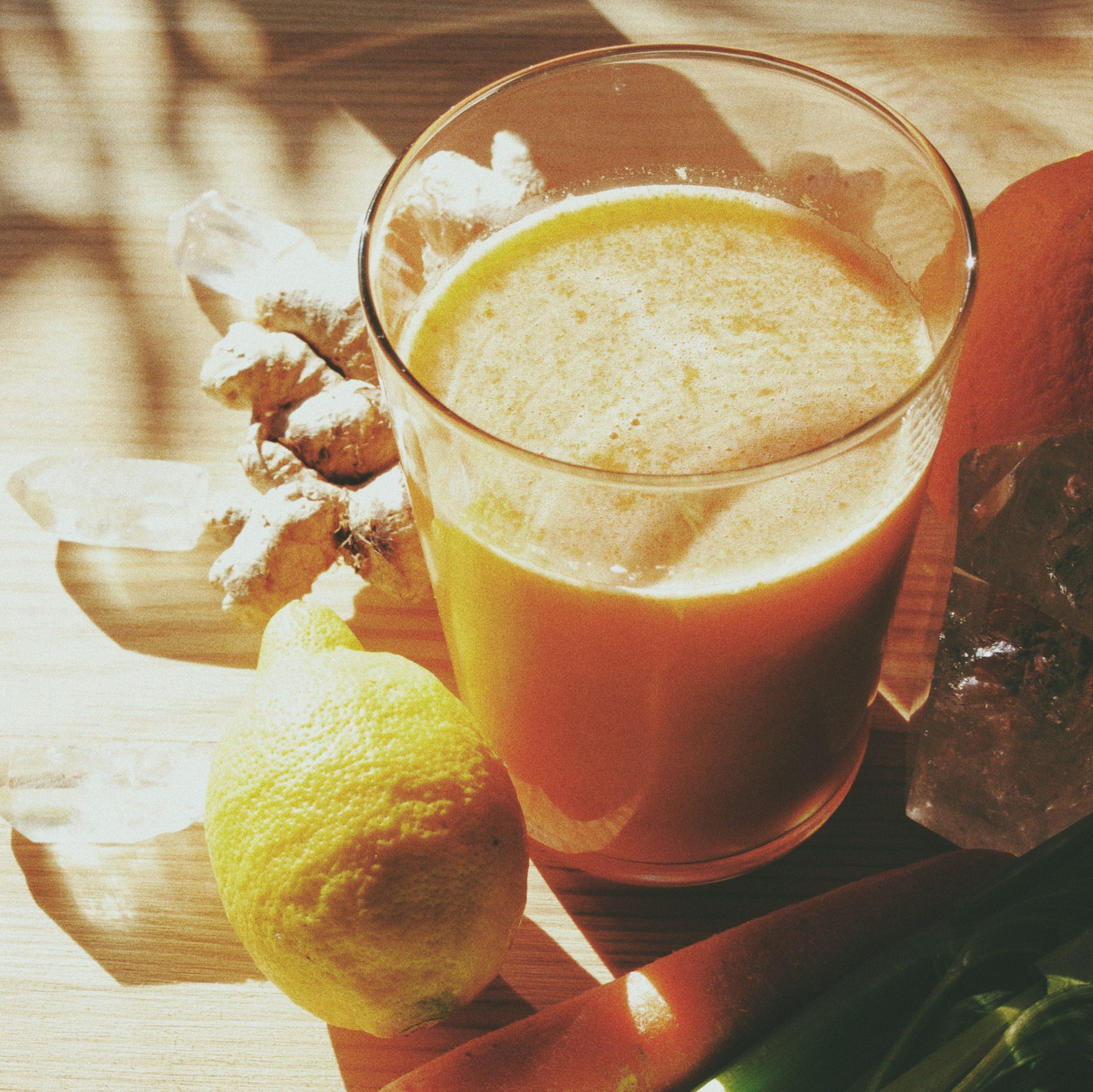 bodegón de zumo multivitamínico reconstituyente de naranja, limón, jengibre y apio